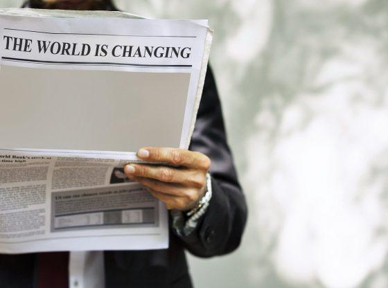 """Businessman hält Zeitung mit dem Titel """"The world is changing"""" in der Hand (pixabay)"""